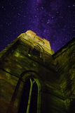 Church tower against a starry sky. Low angle view of a stone church tower with decorative windows reaching up towards a starry night sky Stock Image
