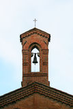Church tower with bell and cross. Brick church tower with bell and cross with arch Stock Photo