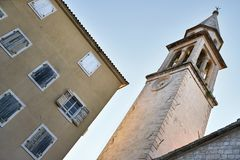 Church tower with clock on facade in Budva in Montenegro stock photo