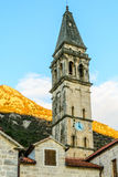 The church tower with a clock in the old town of Perast, Montene. The church tower with a clock in the old town of Perast royalty free stock photography
