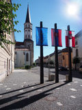 Church tower and flags in Levoca. Summer view portraying tower of historical church in Levoca, with flags of European Union, Slovakia and flag of Levoca town in Royalty Free Stock Photography