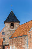 Church tower and historic house in Greetsiel. Germany Royalty Free Stock Photography
