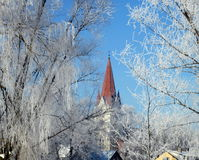 Church tower and houses, Lithuania. Evangelical church tower and houses roofs in winter in Silute town, Lithuania Stock Image