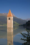 Church tower at lake Reschen Royalty Free Stock Image