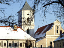 Church tower and monastery. Snow on the roof of the church and convent Stock Photos