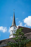 A church tower at the old center of Vienna. Above the tile roofs and a tree on a sunny summer day Royalty Free Stock Photos