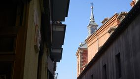 Church tower overlooks dark alley in Madrid royalty free stock photos