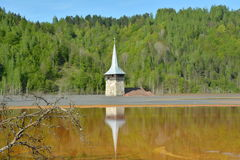 Church tower refelction in the lake of Geamana in the Apuseni Mountains, Romania Stock Photos