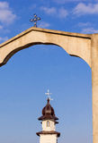 Church tower seen through the arch gate Stock Image