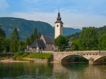 Church tower and stone bridge at Lake Bohinj Stock Photo