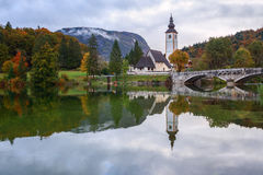 Church tower and stone bridge at Lake Bohinj stock images
