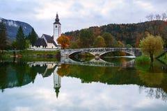 Church tower and stone bridge at Lake Bohinj royalty free stock images