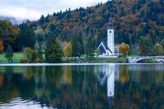 Church tower and stone bridge at Lake Bohinj stock photography