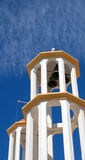 Church tower in white yellow with bells and blue sky Royalty Free Stock Photo