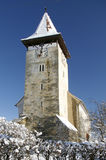 Church tower in winter transylvanian village. Of Cisnadioara Romania roof covered with snow sunny day Royalty Free Stock Photos