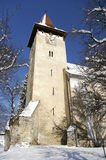 Church tower in winter transylvanian village. Of Cisnadioara Romania roof covered with snow sunny day Royalty Free Stock Images