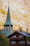 Church tower and wooden chalet in Zermatt Royalty Free Stock Photography