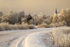 Church and trees in the snow. Church, trees and road in the snow stock photo