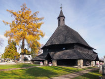 Church in Tvrdosin, UNESCO landmark. Autumn view of yellow tree and wooden church of All Saints (Kostol Vsetkych svatych) in Tvrdosin town, northern Slovakia Royalty Free Stock Image