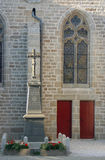 Church with two red doors. Stained glass panel and a statue Royalty Free Stock Photos