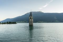 Church under water, drowned village, mountains landscape and peaks in background. Reschensee Lake Reschen Lago di Resia. Royalty Free Stock Photos