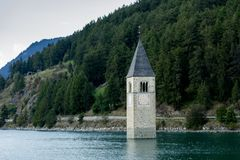 Church under water, drowned village, mountains landscape and peaks in background. Reschensee Lake Reschen Lago di Resia. Stock Photos