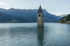 Church under water, drowned village, mountains landscape and peaks in background. Reschensee Lake Reschen Lago di Resia. stock photography