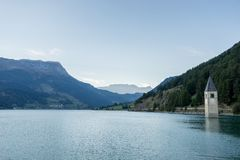 Church under water, drowned village, mountains landscape and peaks in background. Reschensee Lake Reschen Lago di Resia. Royalty Free Stock Photography
