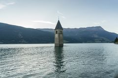 Church under water, drowned village, mountains landscape and peaks in background. Reschensee Lake Reschen Lago di Resia. Royalty Free Stock Images