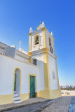 Church in the village of Ferragudo. View of the bell and cross religious. Stock Images