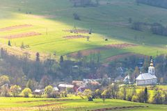 Church and village in green spring mountain valley Royalty Free Stock Images