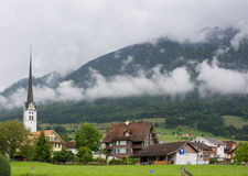 Church and village in Switzerland. Small country village with mountains and low clouds Royalty Free Stock Photos