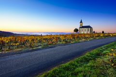 Church, vineyards and road of Saint Laurent d'Oingt during sunri Royalty Free Stock Photo