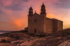 The Church of Virgen de la Barca, Muxia, Galicia, Spain. Shot at sunset, lots of orange and purples in the sky from a low angle royalty free stock image