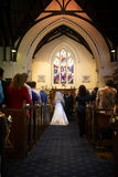 Church Wedding I. A bride and her father walk down the aisle of a traditional church to an expectant groom Royalty Free Stock Images