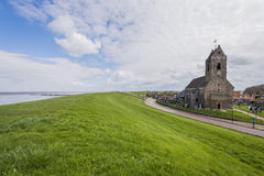 Church of Wierum with Dike, Friesland. Wierum, The Netherlands - April 18, 2016: Church of Wierum with Waddensea dike in Friesland in the Netherlands Royalty Free Stock Photo