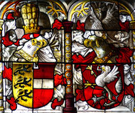 Church window. Inside the cathedral of cologne showing emblem and knight motives in red and yellow stock image