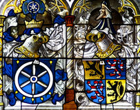Church window. Inside the cathedral of cologne showing emblem and knight motives in blue and yellow royalty free stock photography