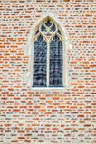 Church window. In the middle of a brick wall Royalty Free Stock Image