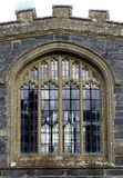 Church window. An old, arched church window, mullioned and leaded, set in stone wall, with view through to opposite window Stock Image