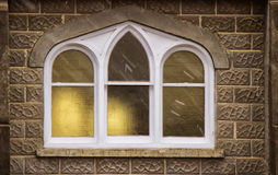 A church window. A white framed church window reflecting a yellow glow Stock Images