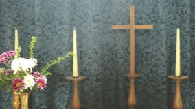 Church Wooden Cross Between Candles And Flowers. Shallow depth of field stock video