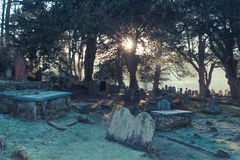 Church yard in winter. Church yard and grave stones in winter, with sunlight coming through the trees Royalty Free Stock Photos