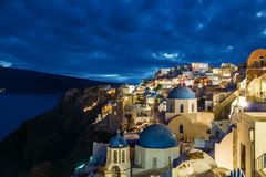 Churches of Oia village at dusk with dramatic sky, Santorini Stock Photography