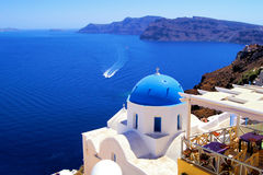 Churches of Santorini. Blue dome church with boat, Oia village, Greece Royalty Free Stock Photography