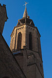 Churchtower with weathervane. In Utrecht, Holland. On top of the spire is a golden weathervane, crowned with a rooster. Brick building with copper rooftiles Stock Photography