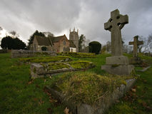 Churchyard. A moody view of a churchyard showing the church and gravestones Stock Photography