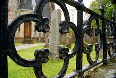 Churchyard with headstone through railing Royalty Free Stock Image