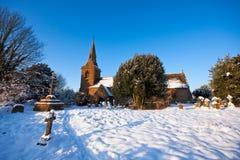 Churchyard inglese tradizionale del villaggio in neve immagini stock libere da diritti