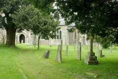 Churchyard and path. Little used side entrance pathway to St James Church in Christow on Dartmoor with gravestones and overhanging trees royalty free stock photos